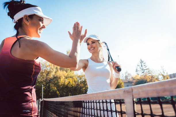 Women giving high five after a good match of tennis stock photo