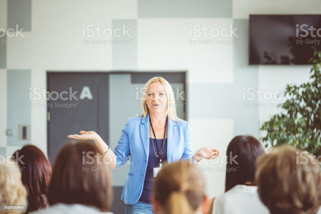 Women giving speech during seminar Mature woman giving speech during conference for businesswomen. Achievement Stock Photo