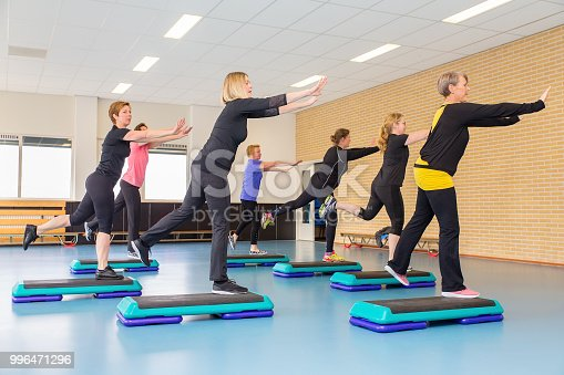 Group of middle-aged caucasian women playing sports in gym class. These dutch persons are training during sports lesson indoors. They use a sport object step up to exercise certain moves. In this way they train their muscles and that keeps them healthier.