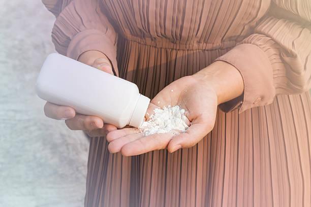 women hand apply talcum powder - talk stockfoto's en -beelden