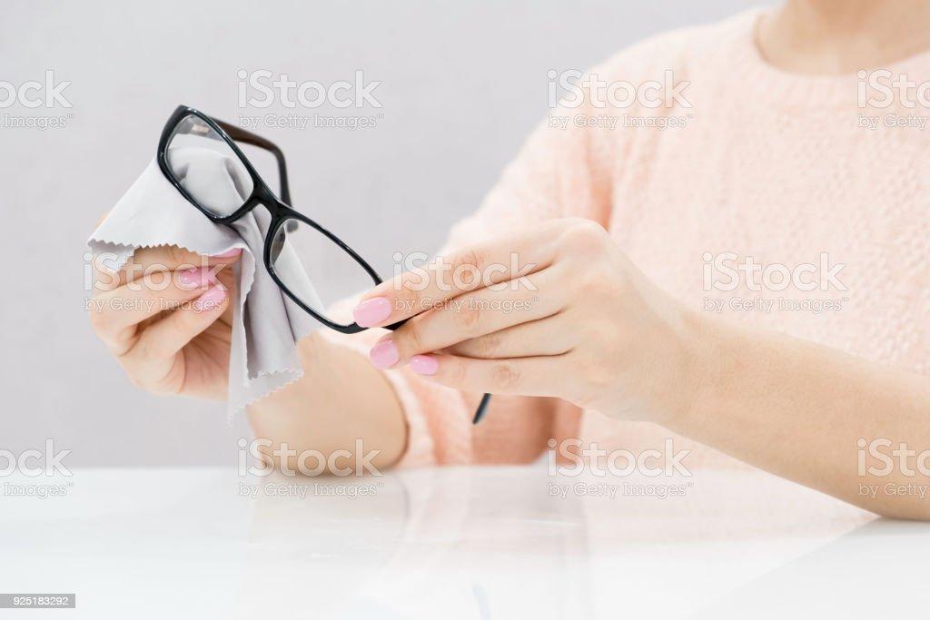 Frauen die hand Reinigung trendige schwarze Brille Kontaktlinsen mit weißen Mikrofaser-Gewebe. Weichzeichnen Sie Hintergrund. Selektiven Fokus – Foto