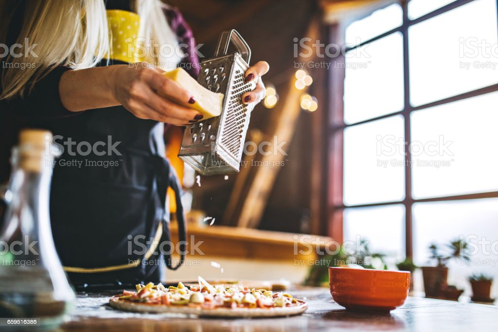 Women hand grating the cheese on the pizza stock photo