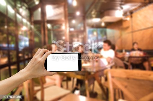 Women hand hlod the smart phone with white blank screen infront of the blur people in the cafe