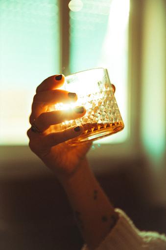 Women hand holding an alcoholic drink backlit sun