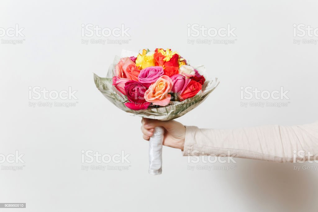 Women hand holding beautiful bouquet of colorful roses, different red, yellow, orange flowers. Isolated on white background. St. Valentine's Day or International Women's Day, holiday concept. stock photo