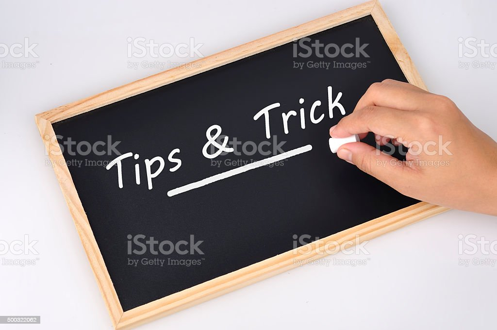 Women Hand Holding Chalk Writing 'Tips and Trick' stock photo