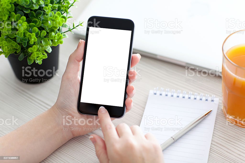 Women hand holding phone with isolated screen above the desk stock photo