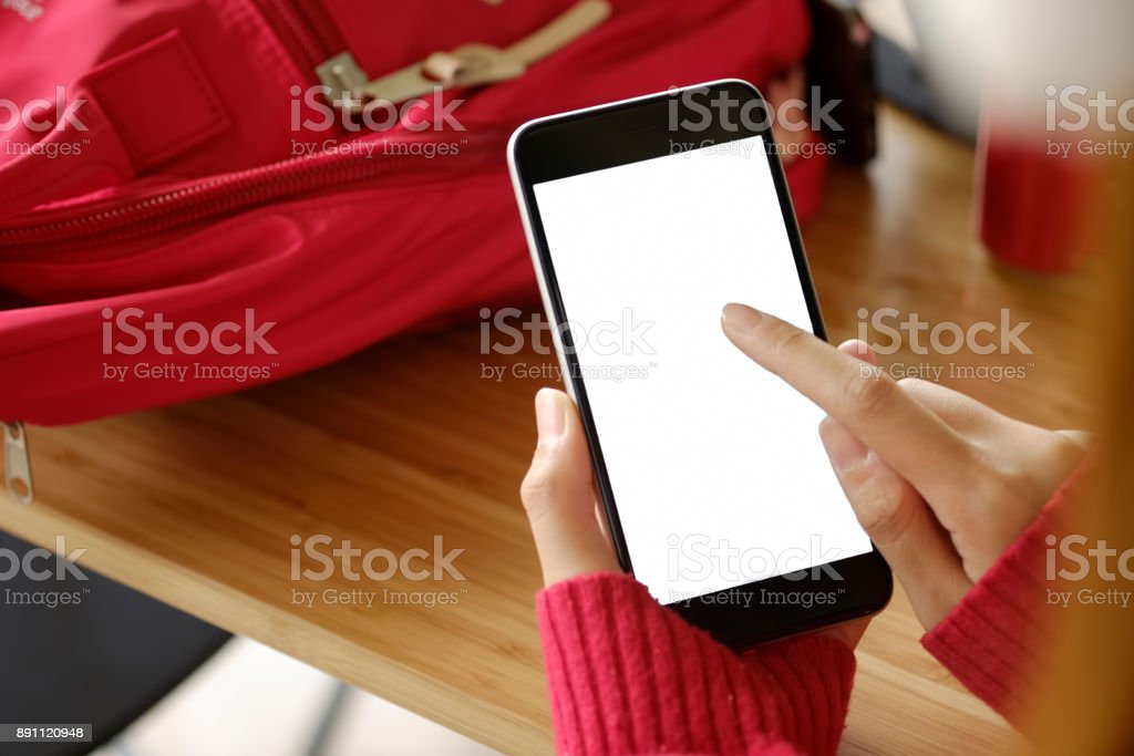 Women hand holding the phone with isolated screen above the desk. stock photo