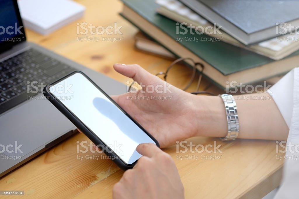 Women hand holding the smartphone with isolated screen above the desk in office royalty-free stock photo