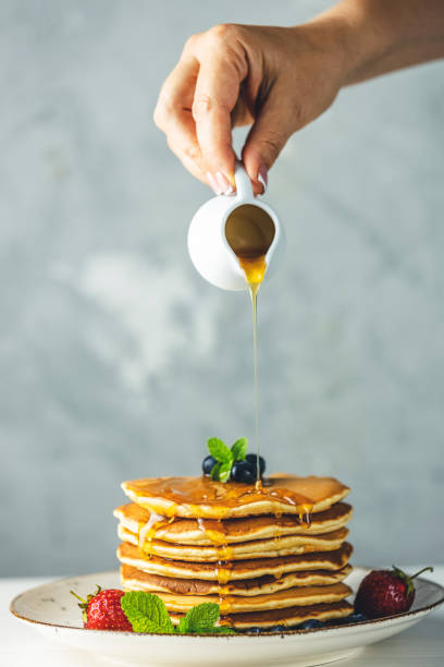 Women hand is pouring syrup from small ceramic jar to pancake with srtawberry, blueberry and mint stock photo