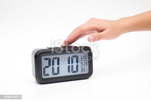 istock Women hand open light at digital table clock 1058434374