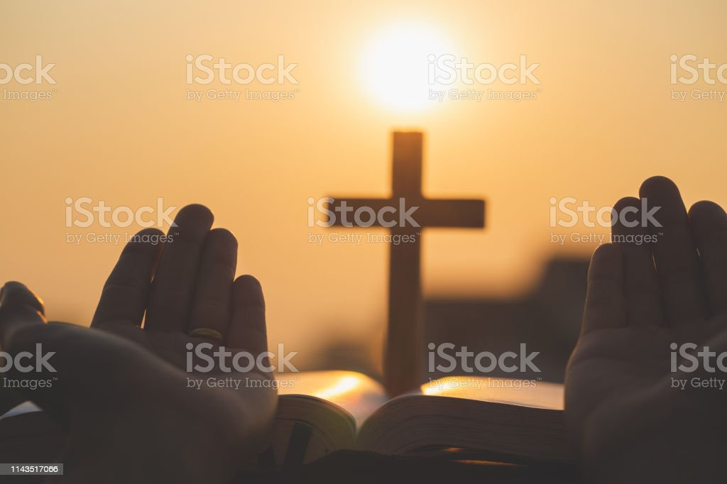 Women hand pray to God with the Bible and the cross of the morning....