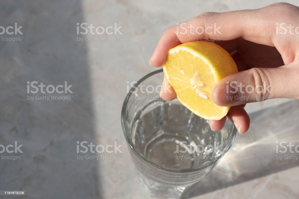 Women hand squeezes lemon juice in glass with soda water on marble table background. Detox healthy drink concept Women hand squeezes lemon juice in glass with soda water on marble table background. Detox healthy drink concept Adult Stock Photo