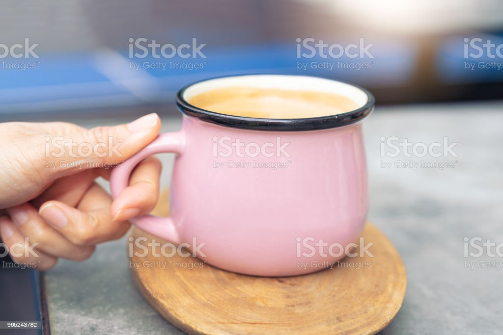 women hand touch pink cup of hot coffee on wooden plate royalty-free stock photo