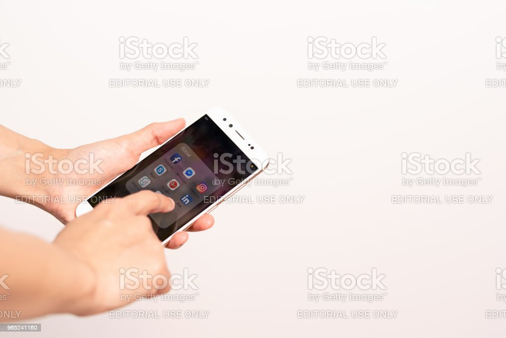 Women hand touching smartphone screen with icons of social media, smartphone life style zbiór zdjęć royalty-free