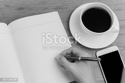 Women hand writing on an empty book with hot coffee and smart phone in black and white