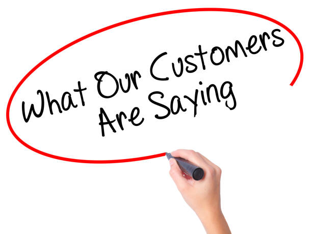 women hand writing what our customers are saying with black marker on visual screen - testimonial stock photos and pictures