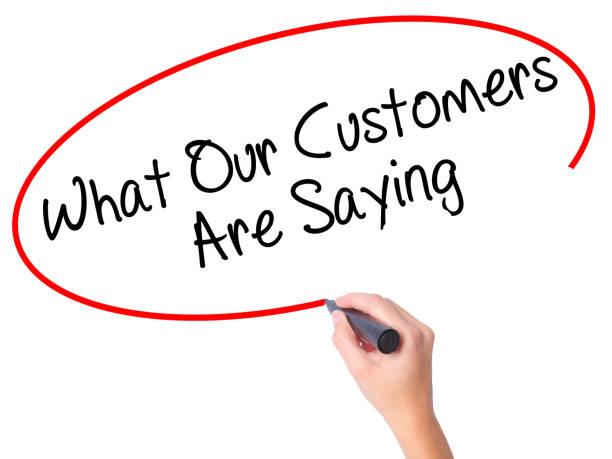 Main de femmes écrit ce que nos clients disent avec marqueur noir sur l'écran visuel - Photo