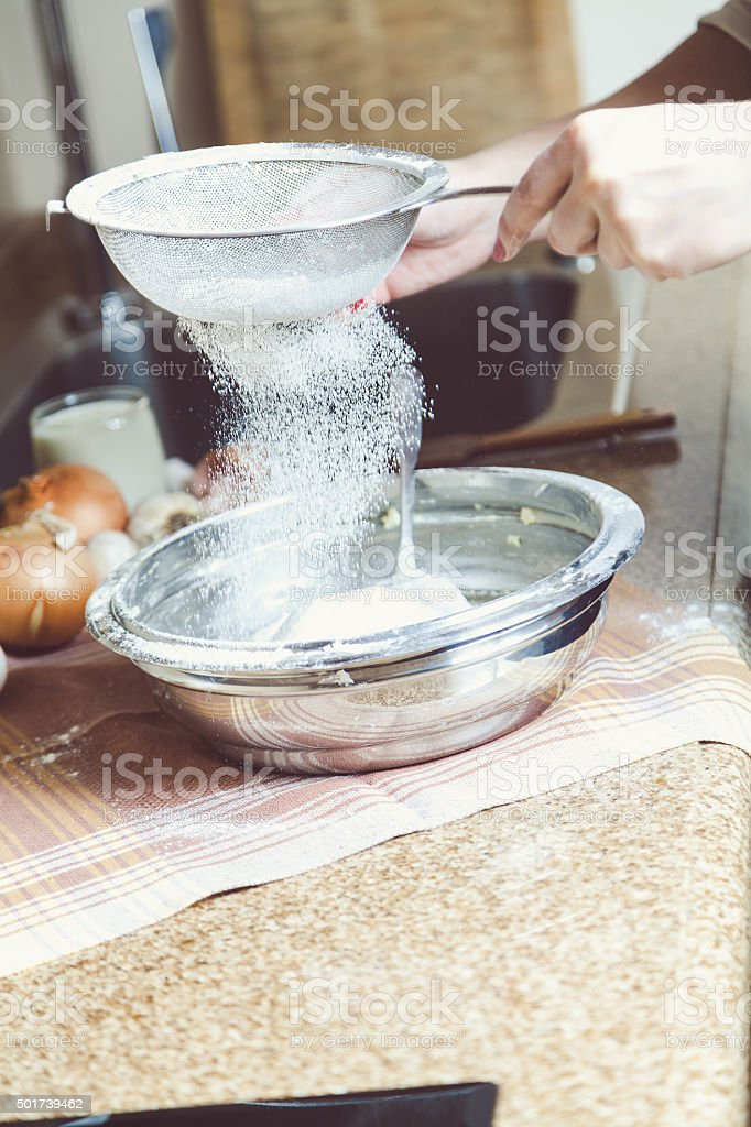 Women hands are holding sieve and sift flour stock photo