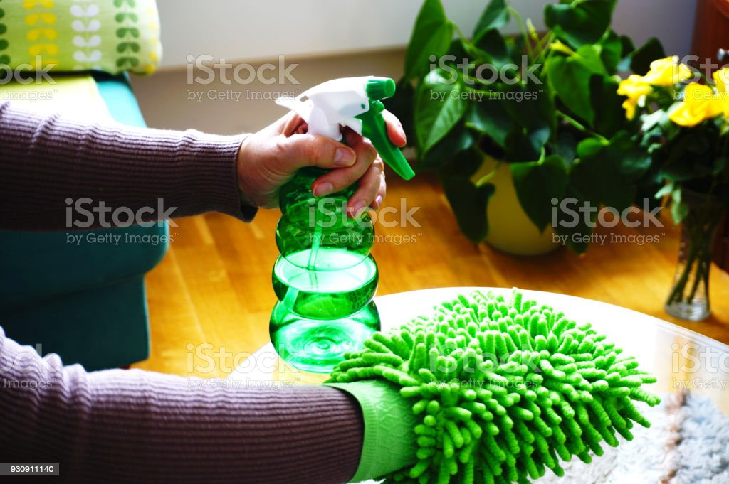 Women hands clean glass table in the living room with green cloth for  cleaning and environmental detergent - Stock image . 01a4b9d691