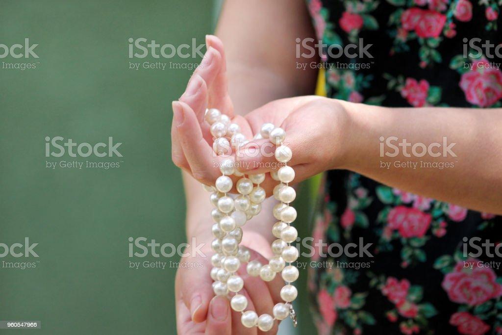 Mãos de mulheres com joias de pérola. Closeup da mão feminina com joia da pérola. Feminino mão segurando um colar de pérola. Pérola na mão da mulher. Colar de pérola branca. Moda e beleza. - foto de acervo