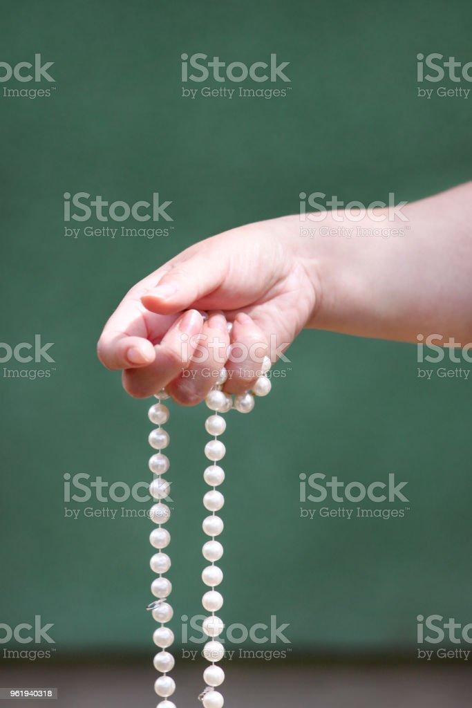 Mãos de mulheres com joias de pérola. Closeup da mão feminina com joia da pérola. Feminino mão segurando um colar de pérola. Colar de pérola branca. Moda e beleza. - foto de acervo