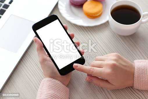 936543982 istock photo Women hands holding phone isolated screen with coffee and laptop 933389888