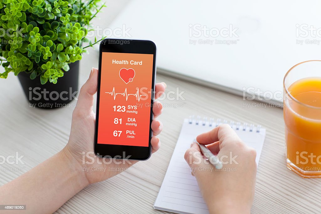 Women hands holding phone with app for health card monitoring stock photo