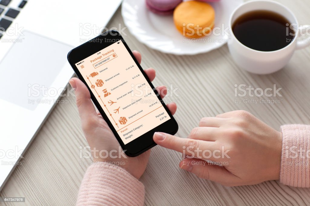 Women hands holding phone with app tracking delivery package stock photo