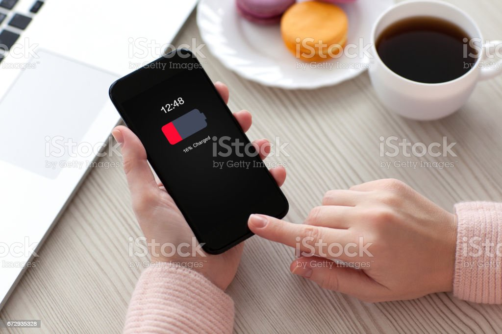 Women hands holding phone with low charged battery screen stock photo