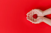 istock Women hands  holding red heart on red background, top view with space for text. world heart day concept 1270044274