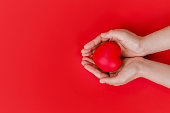 istock Women hands  holding red heart on red background, top view with space for text. world heart day concept 1270046564