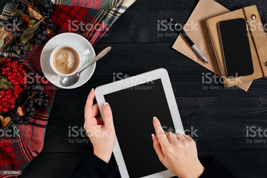 Women hands holding the tablet with black screen above the table with a cup of coffee and smart stock photo
