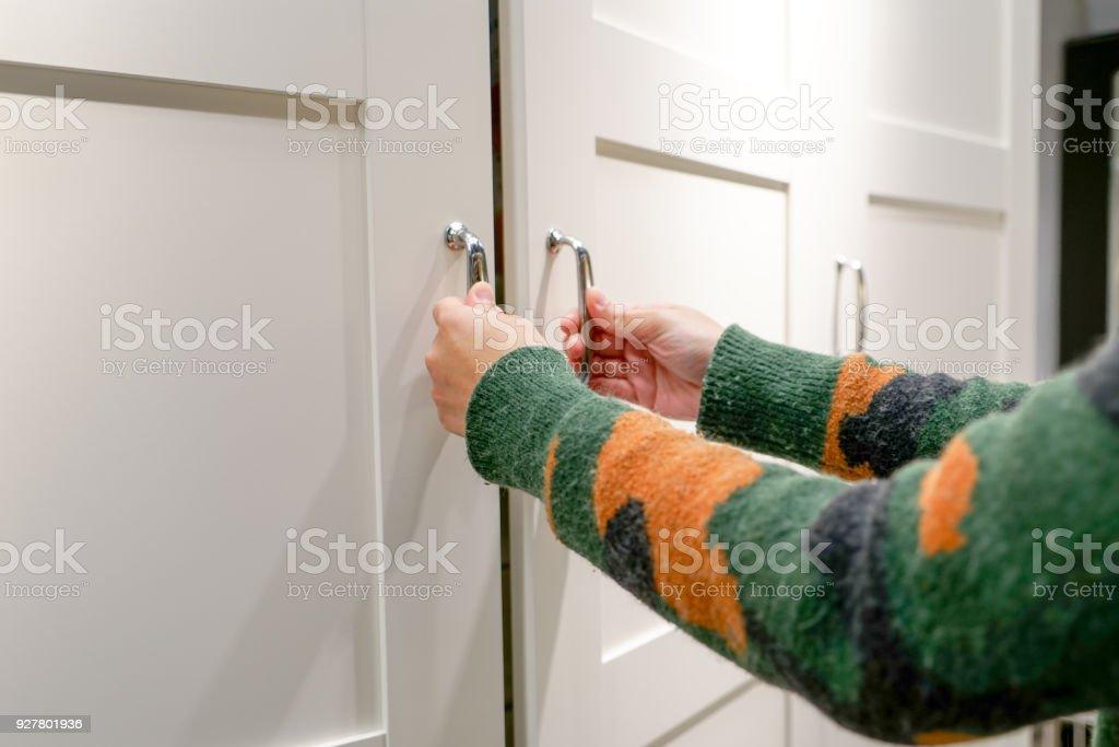manos de las mujeres abren la puerta del armario/armario, puerta de madera blanca - foto de stock
