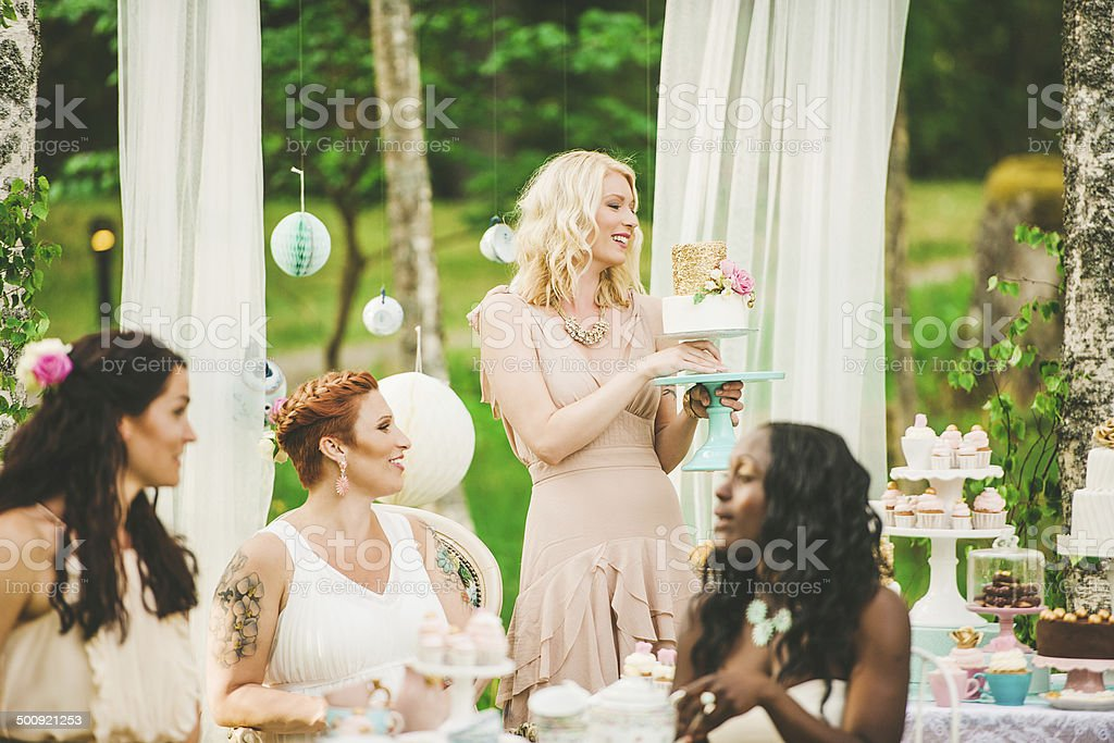 Women having a garden party with dessert table stock photo