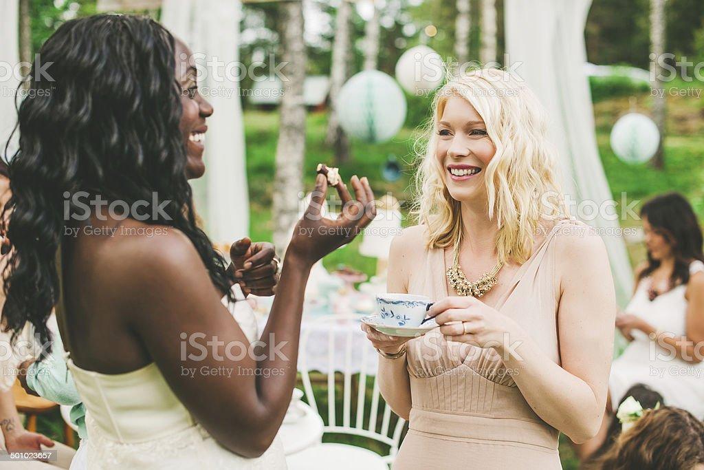 Women having a garden party with dessert table stock photo