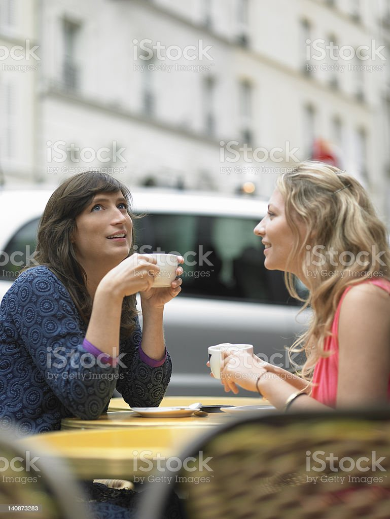 Women having coffee at sidewalk cafe stock photo