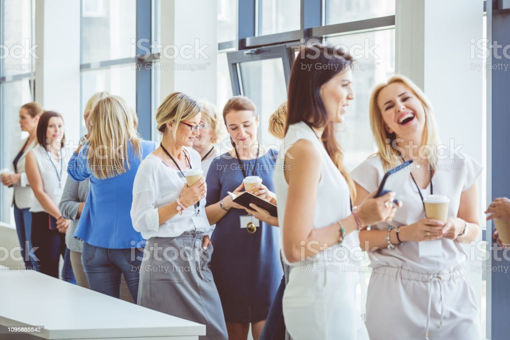 Women having conversation during a break. Group of women having conversation during a break. Coffee break during a women conference. Adult Stock Photo