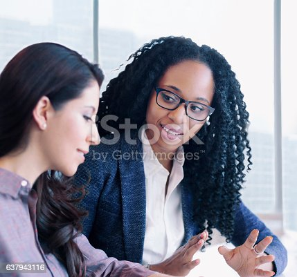 istock Women having conversation together in business office 637943116