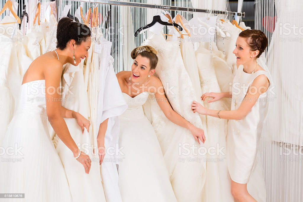 Women having fun during bridal dress fitting in shop stock photo