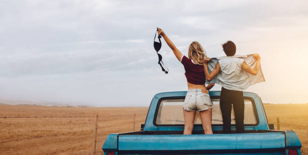 Women having fun traveling by pickup truck Rear view of two woman standing in the back of a open truck while traveling to country side. Woman holding her bra with friends standing with unbuttoned shirt. undressing stock pictures, royalty-free photos & images