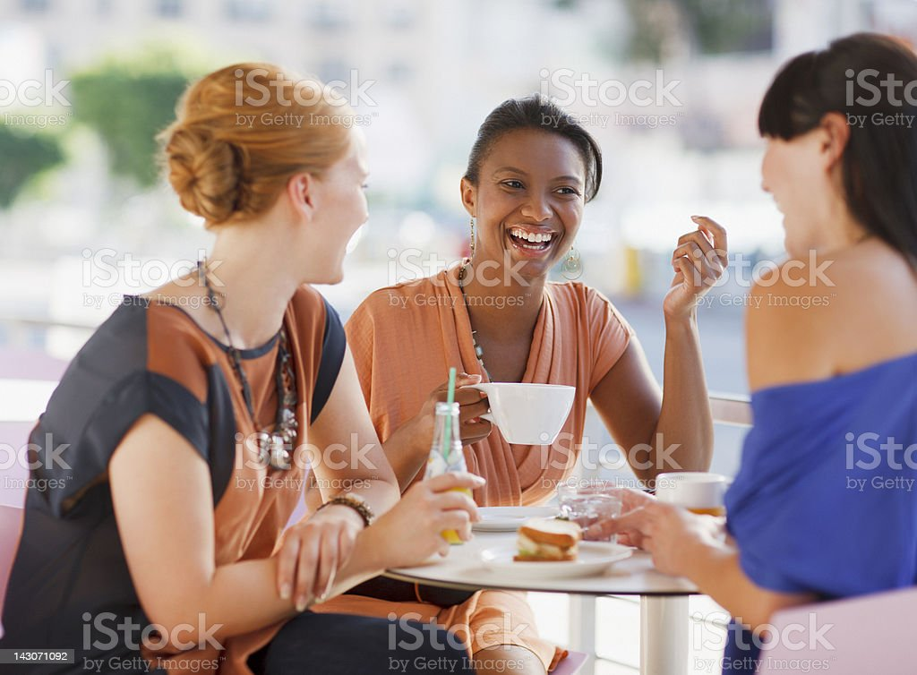 Women having lunch together in cafe stock photo