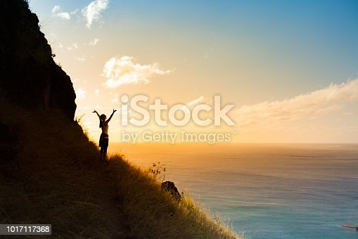 Women hiker enjoying beautiful sunset view from the mountain cliff.