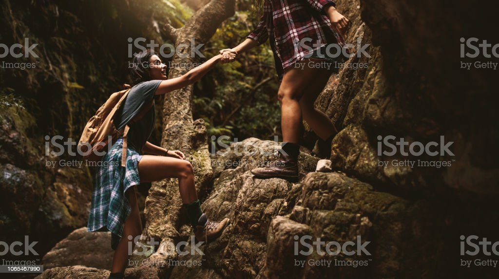 Woman holding hand of female friend while climbing a rock during...