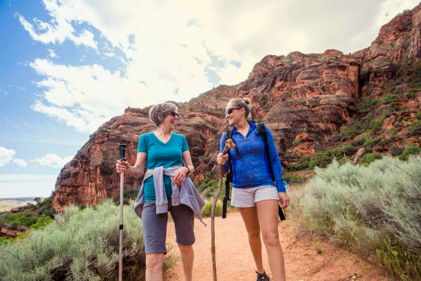 frauen, die zusammen in einem schönen roten rock canyon wandern - happy trails stock-fotos und bilder