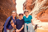 Three happy people hiking together in a red rock sandstone slot canyon in the deserts of Utah on an adventure vacation. Two women and a girl smiling and posing together during a fun hike