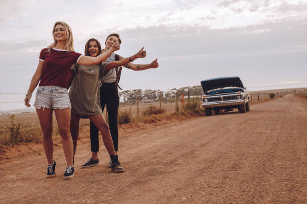women hitchhiking near their broken car on country road - stranded stock pictures, royalty-free photos & images