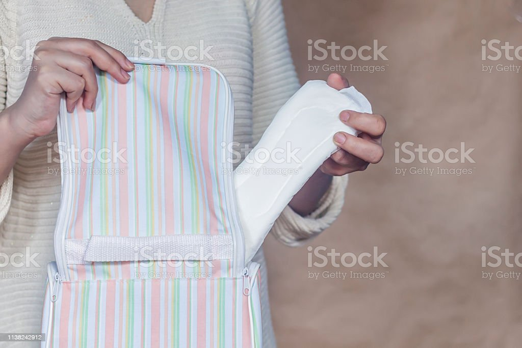 Women hold a menstrual pad. Young woman taking out a sanitary pad...