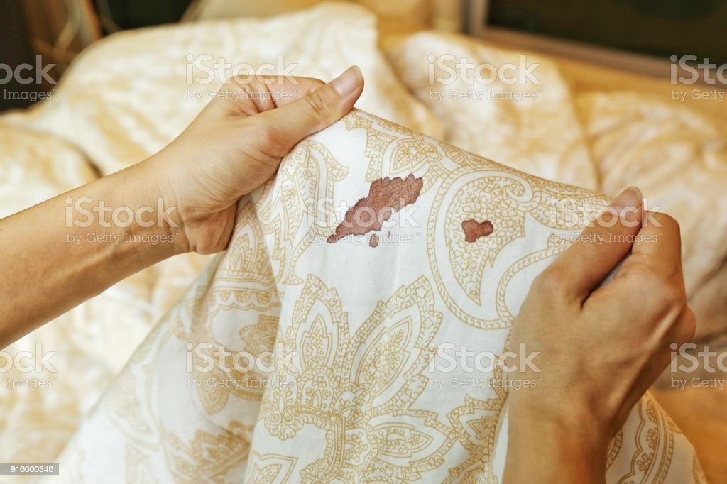 Women hold bed sheet with period blood spot stains on blur background. Need to be cleaning. stock photo