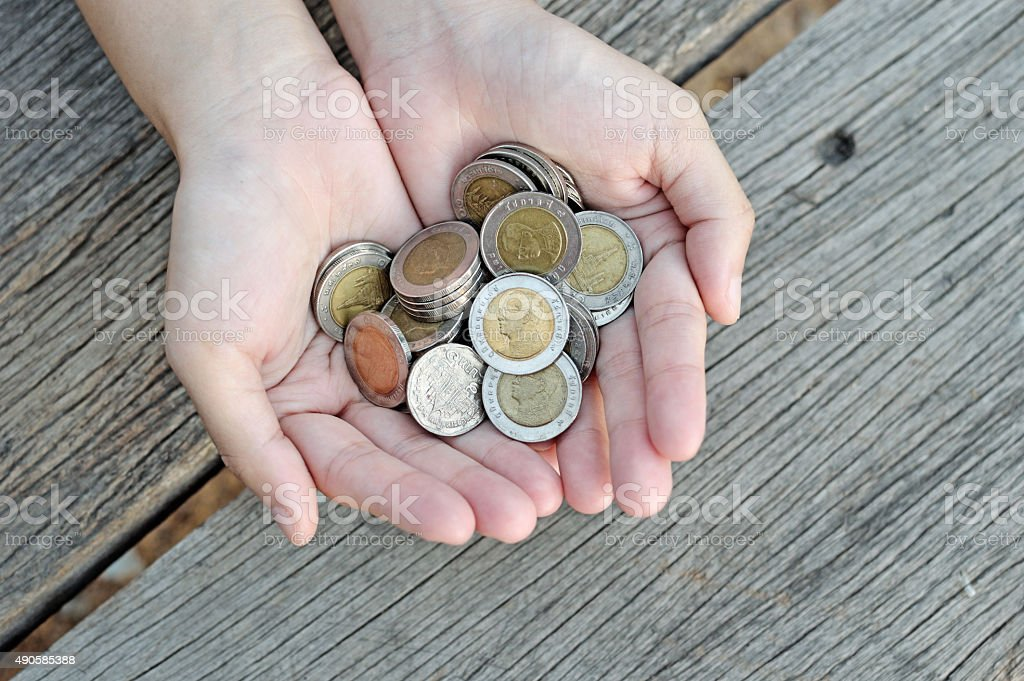 Women hold  coins on wood table stock photo